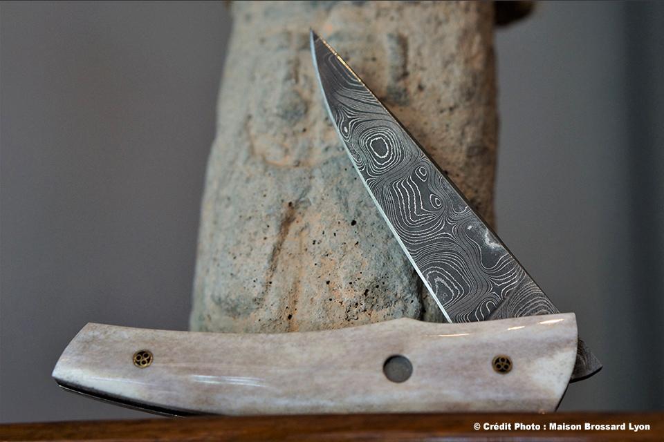 A&J Chomilier. Lame Damas carbone artisanal (C.Nichols). Fenêtre Damas carbone (Styrefors). Manche bois de renne. Étui autruche. 1050 €